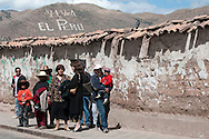 "People wait for the bus on a street in Cusco, Peru, beneath the ""Viva El Peru"" sign, etched into the hillside south of the city."