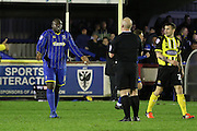 Bayo Akinfenwa of AFC Wimbledon debates with referee S Hooper during the Sky Bet League 2 match between AFC Wimbledon and Dagenham and Redbridge at the Cherry Red Records Stadium, Kingston, England on 24 November 2015. Photo by Stuart Butcher.
