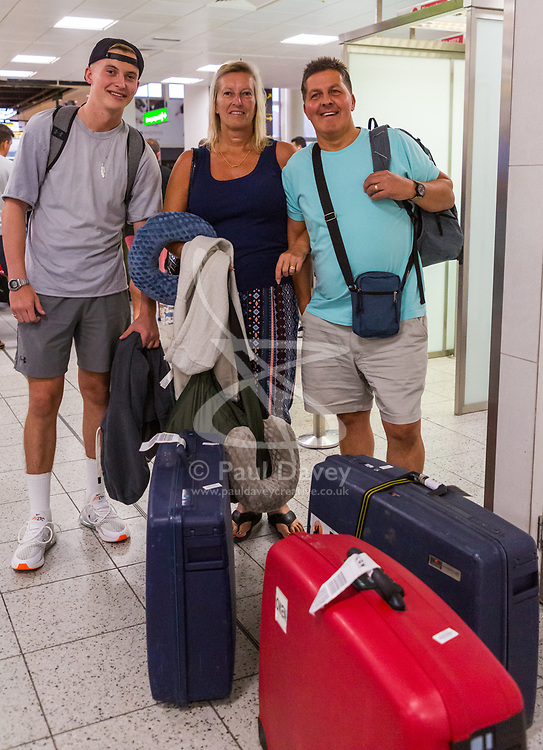 Jonny, 20, Elaine, 56 and Dis Owen arrive back at Gatwick Airport on one of the first repatriation flights for stranded Thomas Cook clients, from Dalaman in Turkey. The travel company ceased trading after failing to come to a deal with its bankers and creditors, leaving tens of thousands of travellers unable to depart on their holidays from South Terminal at Gatwick Airport, and a massive repatriation exercise to return holidaymakers from destinations all over the world. London Gatwick Airport, September 23 2019.