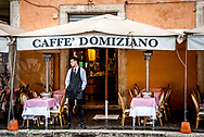 Italian waiter stands outside Caffe Domiziano restaurant on Piazza Navona waiting for customers on a rainy day with empty tables for outdoor dining.