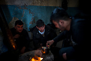 Migrants from afghanistan preparing tea on a wooden stove made from an old barrel in Belgrade train starion makeshif camp. March 17th, 2017, Belgrade, Serbia. Federico Scoppa/CAPTA