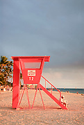 Vertical image of a woman reading a newspaper in Waikiki on a lifeguard stand