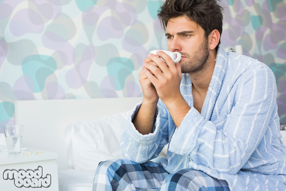 Sick man drinking coffee while sitting on bed at home