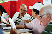 Cuban Dr. Raul Herrera Vald&eacute;z, <br /> discussing patients' medical results<br /> as part of a series of investigations carried out by the 'Nefrolempa' health team.<br /> <br /> Ciudad Romero, Bajo Lempa, El Salvador. 2011.<br /> The 'Nefrolempa' research project is a collaboration between the El Salvador Ministry of Health, the Nephrology Institute of Cuba's Ministry for Public Health and the United Bajo Lempa Committee Association. The aim of the project is to investigate the reasons for the high levels of Chronic Kidney Disease (CKD) suffered by the communities within the Bajo Lempa region. It is exploring whether the use of agrochemicals might be a factor in the prevalence of the disease.<br /> <br /> Medical team: Dr Elsy Brizuela de Jimenez, Directora Unidad de Salud. Miriam Colindres, Nurse. Maria Eraida Velasquez, clinic and laboratory worker. Ecuilia Castro Peraza, Nutritionist. Veronica Contreras, Education for health. Guadelupe Nunez, Psychologist. Luis Diaz General support worker. Dr Raul Herrera Valdes, Nefrologo, Cuba. Dr Miguel Almaguer Lopez, Nefrologo Cuba. Dr Carlos Orantes, Salvadorean Nefrologist. Dr Juan Carlos Awaya, Salvadorean Nefrologist.