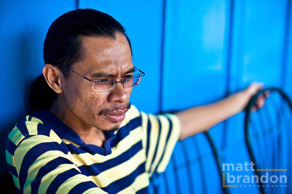 A young man sets pensively against a blue wall at a coffee shop on Jalan Transfer in downtown Georgetown.