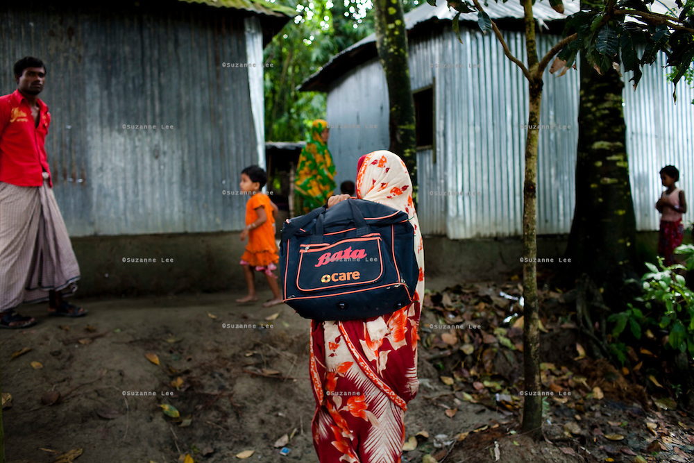 A widow, Rubi Begum, 40, sells her products in Ghagoa Villlage, Gobindagonj Upazila, Gaibandha, Bangladesh on 19th September 2011. Living alone after her husband's passing, she has now (since 2.5 years) found financial independence by working as a saleswoman, earning 3500 - 5000 Bangladeshi Taka per month. She is one of many rural Bangladeshi women trained by NGO CARE Bangladesh as part of their project on empowering women in this traditionally patriarchal society. Named 'Aparajitas', which means 'women who never accept defeat', these women are trained to sell products in their villages and others around them from door-to-door, bringing global products from brands such as BATA, Unilever and GDFL to the most remote of villages, and bringing social and financial empowerment to themselves.  Photo by Suzanne Lee for The Guardian