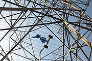 Tangled tricycle hangs in barbed wire of an electricity pylon on an estate in Beckton, East London.