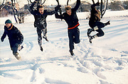 Teenagers leaping in a snowy London park. London, Greenford, UK, 1981.