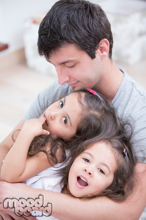 Father with daughters relaxing at home