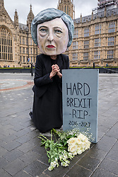© Licensed to London News Pictures. 09/06/2017. London, UK. Campaigners from the organisation Avaaz pose outside Parliament with a Theresa May head and a gravestone mourning the 'death of hard Brexit'. Prime Minister Theresa May failed to secure a parliamentary majority in the 8 June 2017 General Election, which she claimed was needed for effective negotiations for Britain's exit from the European Union.  Photo credit: Rob Pinney/LNP