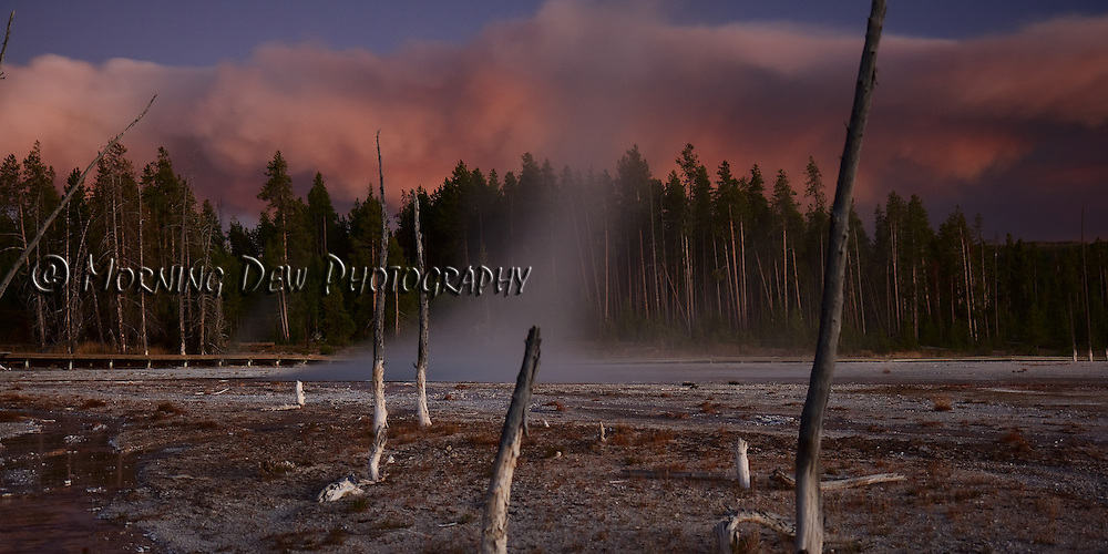 Steam rises from Celestine Geyser against the background of sun-tinted smoke from the Arnica fire in Yellowstone National Park.
