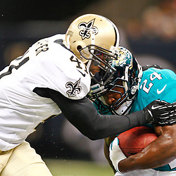 August 17, 2012; New Orleans, LA, USA; Jacksonville Jaguars running back Montell Owens (24) is tackled by New Orleans Saints safety Roman Harper (41) during the first half of a preseason game at the Mercedes-Benz Superdome. Mandatory Credit: Derick E. Hingle-US PRESSWIRE