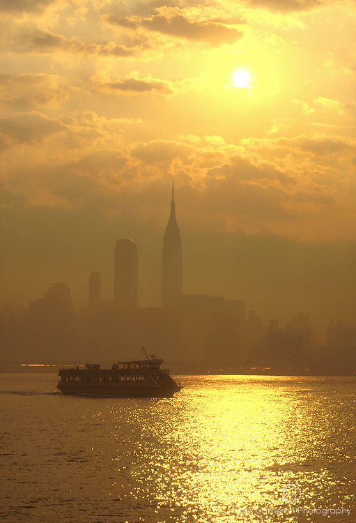 A ferry crosses the Hudson River with the Empire State Biulding behind.<br /> New York, USA.