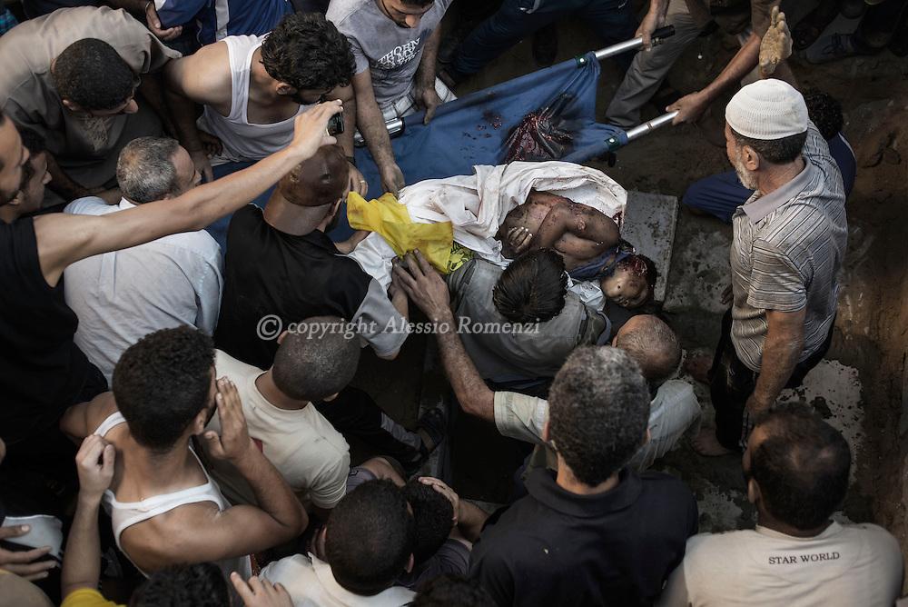 Gaza Strip: Palestinian mourners bury the body of a boy from Bakr family,killed by Israeli naval bombardment in Gaza City, on July 16, 2014. ALESSIO ROMENZI