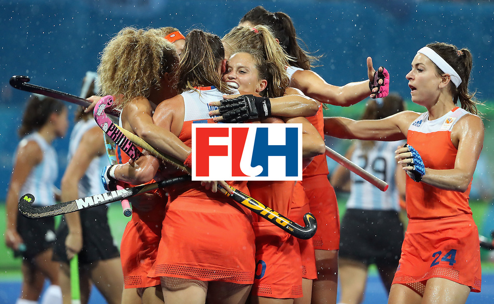 RIO DE JANEIRO, BRAZIL - AUGUST 15:  Kelly Jonker #10 of Netherlands hugs Lidewij Welten #12 with teammates after Welten scored a goal against Argentina during the quarter final hockey game on Day 10 of the Rio 2016 Olympic Games at the Olympic Hockey Centre on August 15, 2016 in Rio de Janeiro, Brazil.  (Photo by Christian Petersen/Getty Images)