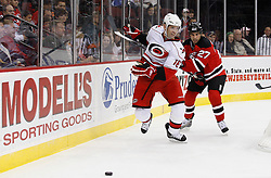 Oct 17, 2009; Newark, NJ, USA; Carolina Hurricanes center Stephane Yelle (18) steps by New Jersey Devils defenseman Mike Mottau (27) during the first period at the Prudential Center.