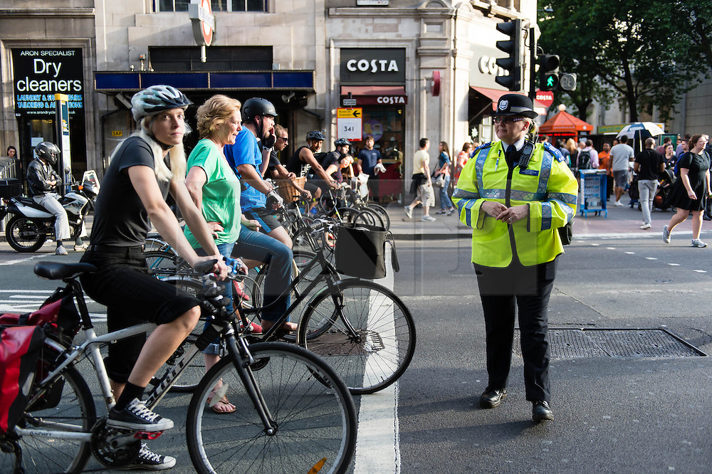 © Licensed to London News Pictures. 21/08/2013. London, UK. A community support officer conducts safety checks on road users at Holborn traffic lights yards from the spot where cyclist Alan Neve was killed by a tipper truck on the 15th July. The checks are to highlight the need to leave room for cyclists at traffic lightsPhoto credit : Richard Isaac/LNP