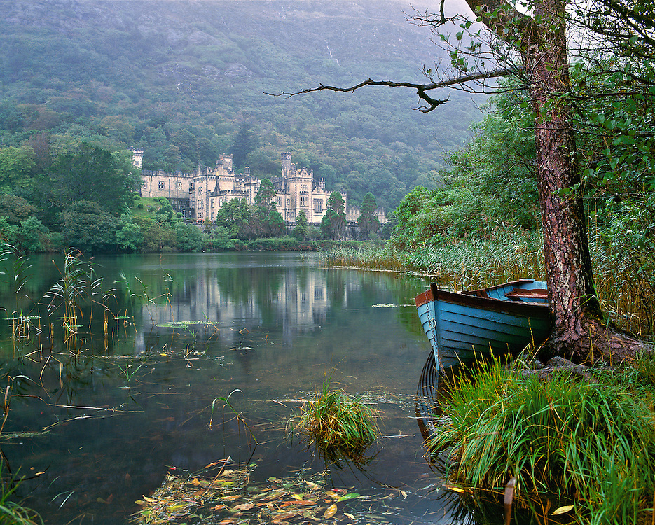 A rowboat rests on a lake below Kylemore Abbey on a rainy day in Connemara, County Galway, Ireland.