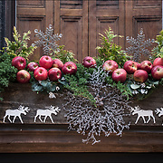 Christmas outdoor apple decorations on front of building in Greenwich Village.<br /> <br /> The tradition of hanging wreath during Christmas is essentially a Christian ritual. This is done during the Christmas season, traditionally used to prepare for the coming of Christ, also known as the Advent season in Christianity.