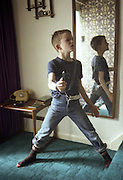 Neville Watson Boy posing inside with flick knife, High Wycombe, UK, 1980s.
