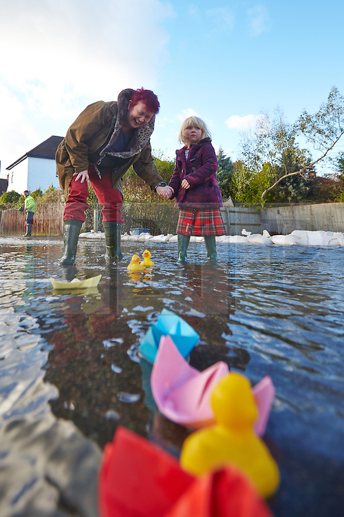 © Licensed to London News Pictures.  09/01/2014. OXFORD, UK. Janie Hampton and granddaughter Delilah Purcell Hampton (4) play with paper boats and rubber ducks in the middle of a flooded street in south Oxford.  Photo credit: Cliff Hide/LNP