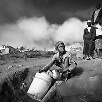 A girl collects water from a denuded hillside in southern Haiti