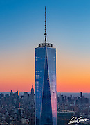 Aerial view of One World Trade Center at sunrise showing the Chrysler Building and the Empire State Building in the background, photographed from a helicopter.