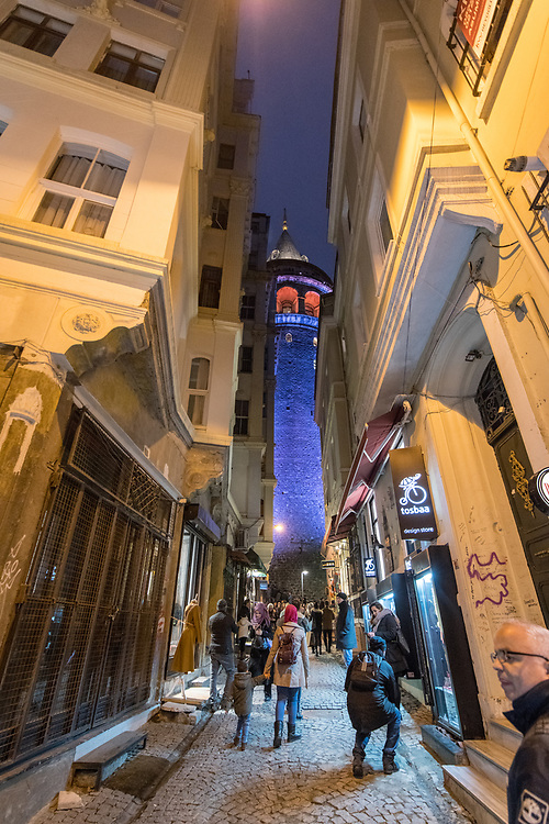 People navigate through narrow street in between buildings with the illuminated Galata Kulesi, a medieval tower built by the Byzantines, looming in the background, Istanbul, Turkey
