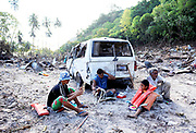 Villagers sit amongst debris in the town of Lalomanu in Samoa. The country was hit by a Tsunami triggered by an earthquake measuring 8.0 on the Moment Magnitude Scale.