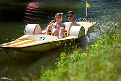 © Licensed to London News Pictures. 19/07/2016. Oxford, UK. A young couple using a paddleboat while enjoying the summer sun on the River Cherwell in the grounds of Oxford University in Oxfordshire, on what is due to be the hottest day of 2016 so far, with temperatures possibly hitting the mid 30's.  Photo credit: Ben Cawthra/LNP