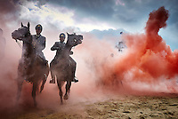 Smoke from grenades shrouds horses and riders during a practice session for members of the Dutch cavalry in Scheveningen, Netherlands, Monday, Sept. 14, 2015. About 80 horses and riders were rehearsing on a beach in the coastal resort of Scheveningen, outside The Hague, for ceremonies which will be held Tuesday to mark the opening of parliament. The horses were exposed to smoke grenades and harsh sounds to reduce their chances of being startled by any incidents during the ceremony. (AP Photo/Phil Nijhuis)
