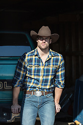hot cowboy in a barn leaning on a truck