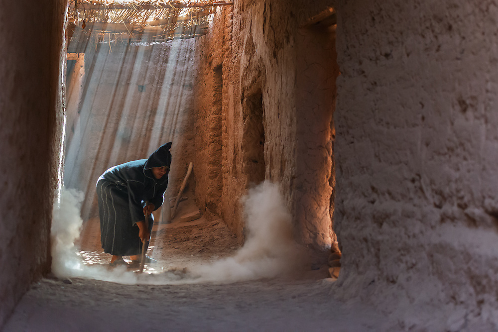A traditional dressed Moroccan man cleans the alley in a Kasbah.