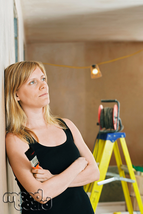Pensive woman leaning against wall ladder in background