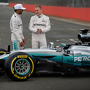 Lewis Hamilton (left) and Valterri Bottas (right) pose with the new Mercedes AMG F1 W8 car on the start/finish straight at Silverstone.  The Mercedes Grand Prix team launch their 2017 F1 W8 Formula One car at a press event held in the Silverstone WIng.