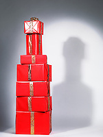 Pile of presents, stacked red Christmas gift boxes in a shape of an alcohol bottle. Alcoholic beverage holiday concept.