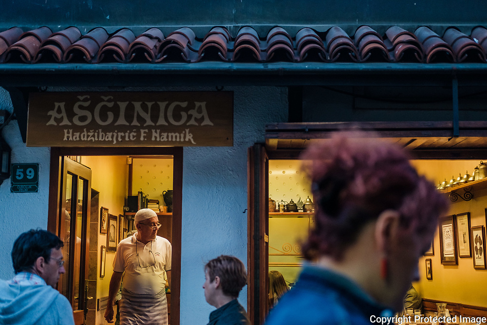 The owner and chef of this traditional Bosnian food, Ašćinica Hadžibajrić ( traditional restaurant )  looks out onto the streets of the old town as evening sets in. This restaurant has been in the family for generations.