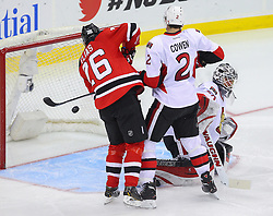 Dec 18, 2013; Newark, NJ, USA;  New Jersey Devils left wing Patrik Elias (26) tries to tip the puck while being defended by Ottawa Senators defenseman Jared Cowen (2) during the third period at the Prudential Center.  The Devils defeated the Senators 5-2.