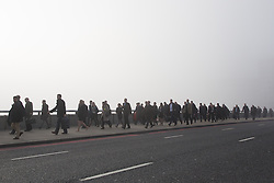 © Licensed to London News Pictures. 13/03/2014. London, UK. Commuters cross London Bridge during thick fog in London this morning, 13th March 2014. Photo credit : Vickie Flores/LNP
