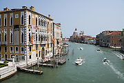 """See Basilica di Santa Maria della Salute from Ponte dell'Accademia bridge on the Grand Canal in Venice, Italy. The bridge links the sestiere of San Marco and Dorsoduro and is named for the Accademia di Belle Arti di Venezia. The original 1854 steel bridge was replaced by a wooden one in 1933 and 1985. Lovers like to attach padlocks (""""love locks"""") to the metal hand rails of the bridge (but are discouraged from doing so by Venice authorities). The yellow and white building at left is Istituto Veneto di Scienze Lettere ed Arti / Palazzo Cavalli Franchetti. Venice (Venezia) is the capital of Italy's Veneto region, named for the ancient Veneti people from the 900s BC. The romantic """"City of Canals"""" stretches across 100+ small islands in the marshy Venetian Lagoon along the Adriatic Sea in northeast Italy, between the mouths of the Po and Piave Rivers. The Republic of Venice was a major maritime power during the Middle Ages and Renaissance, a staging area for the Crusades, and a major center of art and commerce (silk, grain and spice trade) from the 1200s to 1600s. The wealthy legacy of Venice stands today in a rich architecture combining Gothic, Byzantine, and Arab styles."""