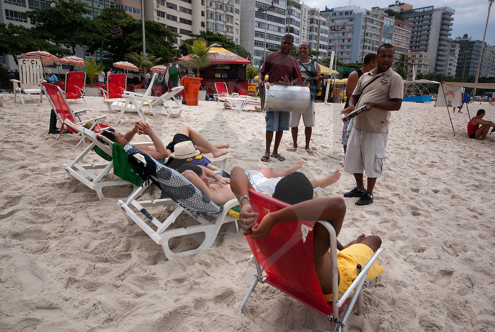 cariocas (natives of rio de janeiro) play music for beach goers on copacabana beach in the city of rio de janeiro, brazil.  the city rises in the background.  such local flair and entertainment abounds in rio.