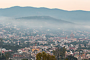 Morning fog rises over the colonial center of San Miguel de Allende, Mexico at dawn.