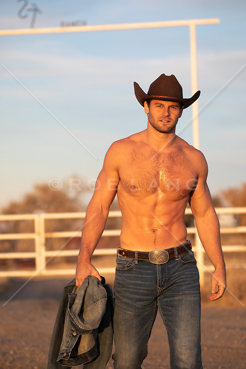 shirtless muscular cowboy on a ranch at sunset
