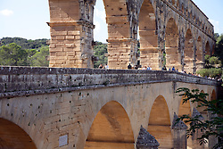Visitors walking across the Pont du Gard.  Built by the Romans circa 19 B.C., this wonder of stone was a major link in a 30-mile canal that brought water to Nimes.  It is the world's second highest standing Roman structure.