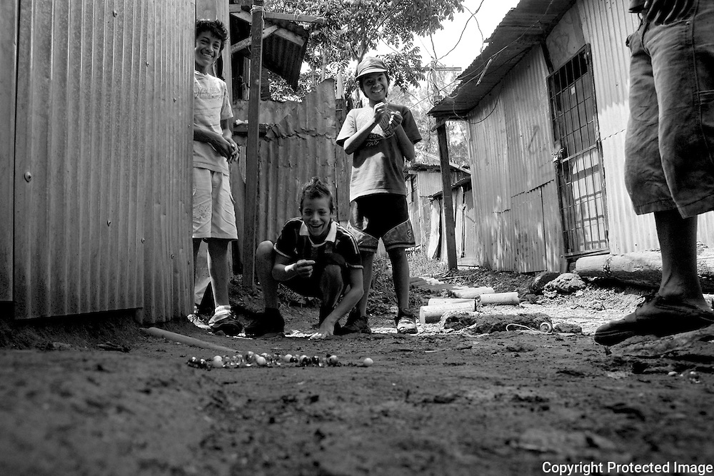 SOme of the boys from San Felipe play a game of marble in the muddy alleys of San Felipe, Costa Rica.