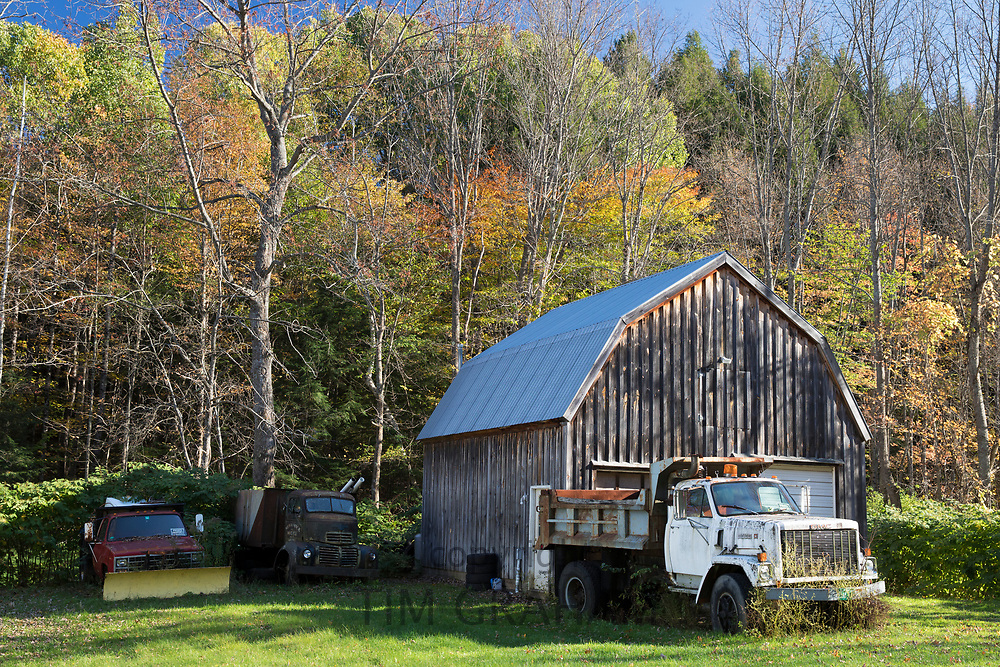 GMC truck and automobiles, one with snow plough, by traditional and typical old barn in Vermont, New England, USA