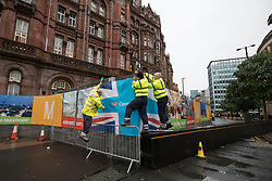 © Licensed to London News Pictures . 01/10/2017. Manchester, UK. Contractors reattach a Conservatives banner which has come away from fencing surrounding the secure zone , at the start of the first day of the conference . The Conservative Party Conference at the Manchester Central Convention Centre . Photo credit: Joel Goodman/LNP