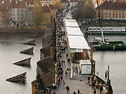 Touristen spazieren ueber die Prager Karlsbruecke welche derzeit saniert wird. Die erste Phase der Sanierung wird bis zum Jahr 2010 dauern. Die Reparatur kostet voraussichtlich mehr als 222 Millionen Kronen kosten.<br /> <br /> Tourists walking across Charles Bridge which is in reconstruction at the moment. The Charles Bridge renovation will be completed in June 2010 and the repairs should prevent water leakage and improve the infrastructure of the bridge and its access roads. Repair works will cost more than 222 million crowns.