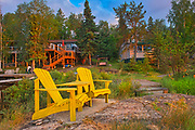 Cottages and Muskoka chairs  at Star Lake at sunrise. Cottage Country Living.<br />