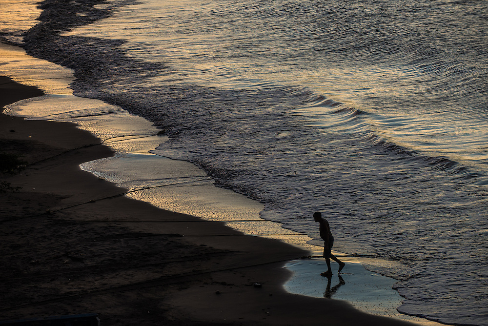 FALCÓN, VENEZUELA - SEPTEMBER 25, 2016: A man walks along the beach used by smugglers to load undocumented migrants on their boats that will illegally take them from Venezuela to Curaçao. Undocumented migrants here have mortgaged property, sold kitchen appliances and even borrowed money from the same smuggling rings that pack them on the floorboards alongside drugs and other contraband. The journey to Curaçao takes them on a 60-mile crossing filled with backbreaking swells, gangs of armed boatmen and coast guard vessels looking to capture migrants and send them home. Then, after being tossed overboard and left to swim ashore, they hide in the brush to meet contacts who spirit them anew into the tourist economy of this Caribbean island. They clean the floors of restaurants, work in construction, sell trinkets on the street, or even solicit Dutch tourists for sex. But at least, the migrants say, there is food. PHOTO: Meridith Kohut for The New York Times